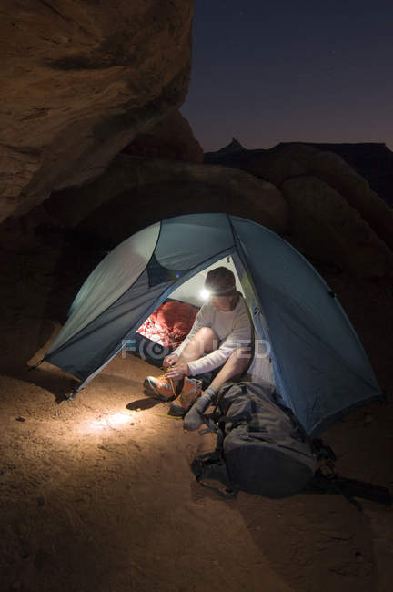 Woman camping at night in tent with headlamp in Indian Creek Canyon, Monticello, Utah — Stock Photo