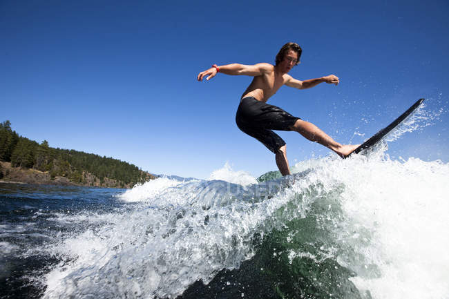 Athletic young man wakesurfing on sunny day in Sandpoint, Idaho — Stock Photo