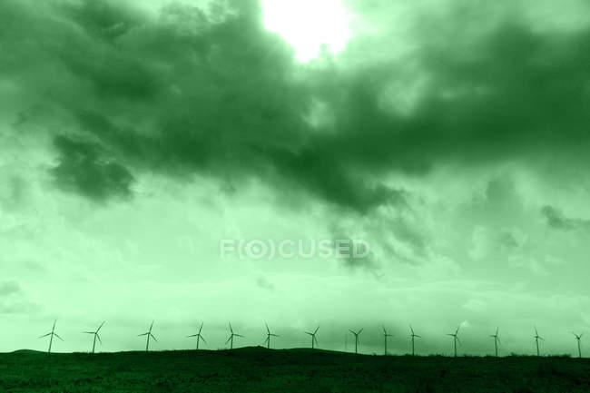 Linha de turbinas de vento sob céu nublado, verde colorida — Fotografia de Stock