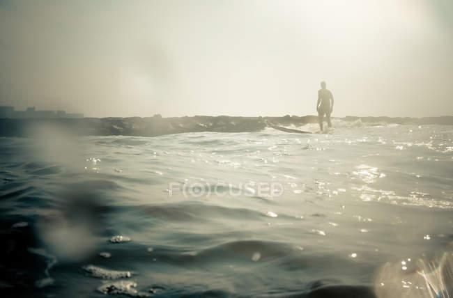Silhouette of surfer on water in bright sunlight — Stock Photo