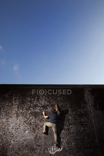 Climber focusing on next move of difficult urban boulder next to Euroborg Stadium in Groningen, Netherlands — Stock Photo