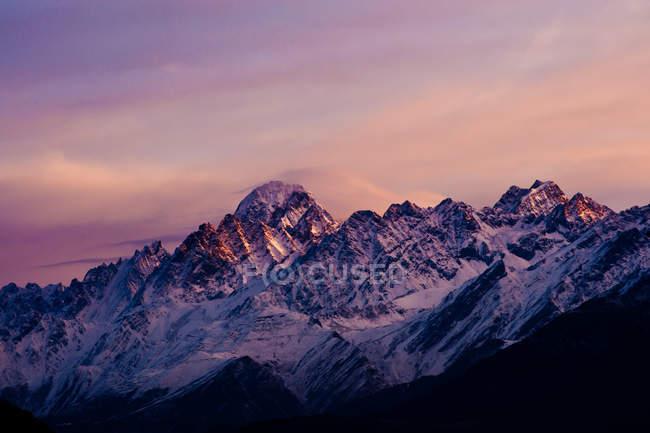 Couvert de neige sommets avec la lumière de l'aube — Photo de stock
