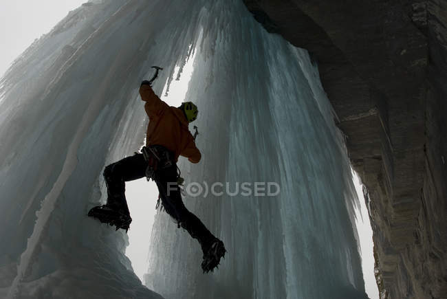 Young male ice climber trying new ice climbing route on large, blue, frozen waterfall, Icefield Parkway, Alberta, Canada. — Stock Photo