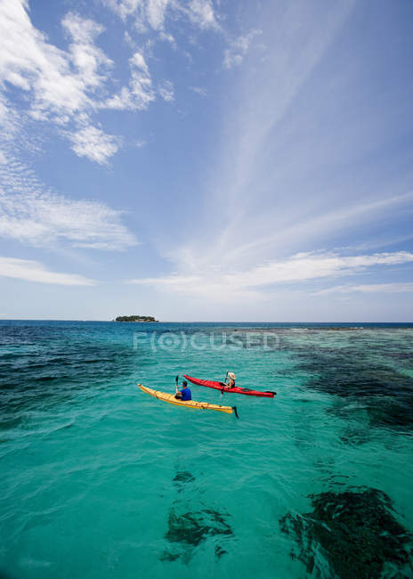 Adult couple in kayaks in clear sea in Ambergris Cay, Belize. — Stock Photo