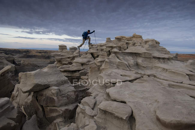 Man hiking and exploring complex sandstone rock formations at Bisti Badlands outside of Farmington, New Mexico — Stock Photo