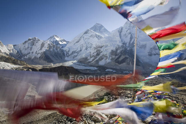 Blurred moving prayer flags with sun lighted mountains — Stock Photo