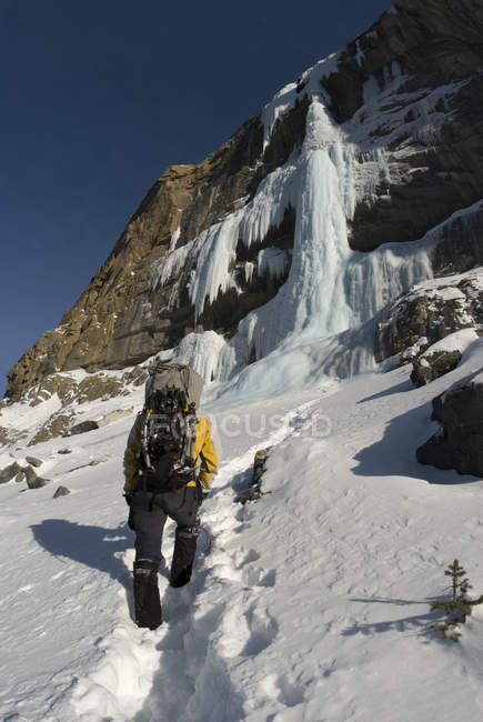 Rear view of ice climber walking with backpack, Alberta, Canada — Stock Photo