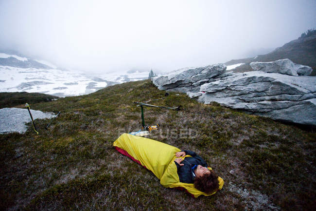 Man sleeping outside in bivy sack underneath cloudy sky in Glacier Peak Wilderness — Stock Photo