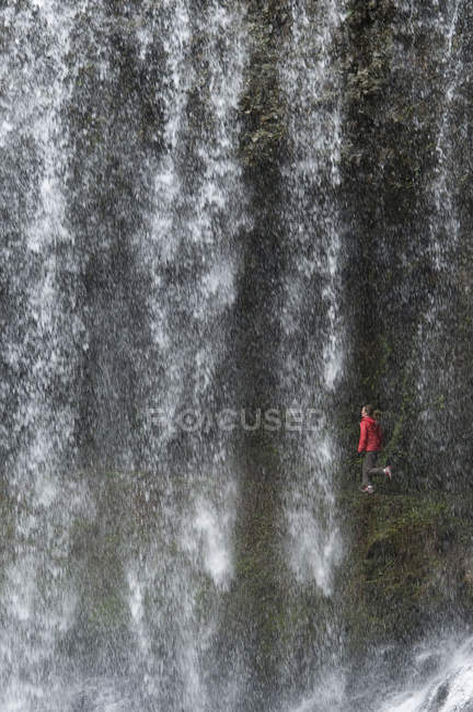 Woman trail running behind waterfall on Ten Falls Trail at Silver Falls State Park — Stock Photo