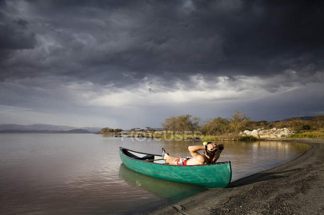 Man lying in canoe on lake shore under cloudy sky — Stock Photo