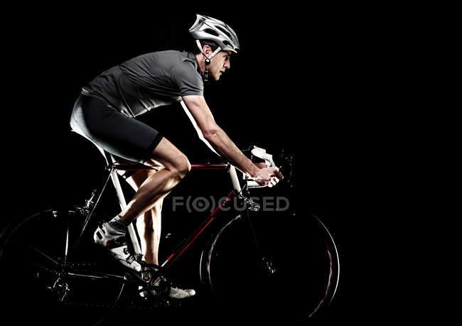 Vista lateral del ciclista de carretera en fondo negro - foto de stock