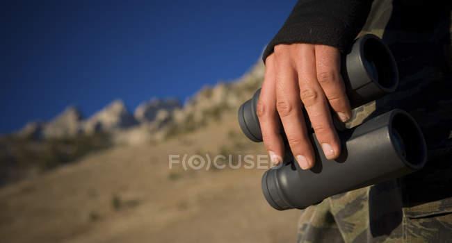 Hiker standing with binoculars surveying surroundings — стоковое фото