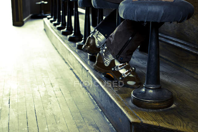 Low angle view of male ski boots at row of bar stools, selective focus — Stock Photo