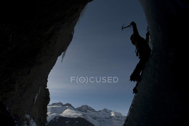 Silhouette of ice climber swinging ice ax on frozen waterfall — Stock Photo