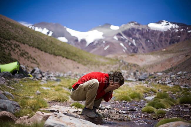 Turista che lava il suo fronte nelle gelide acque del torrente di montagna — Foto stock