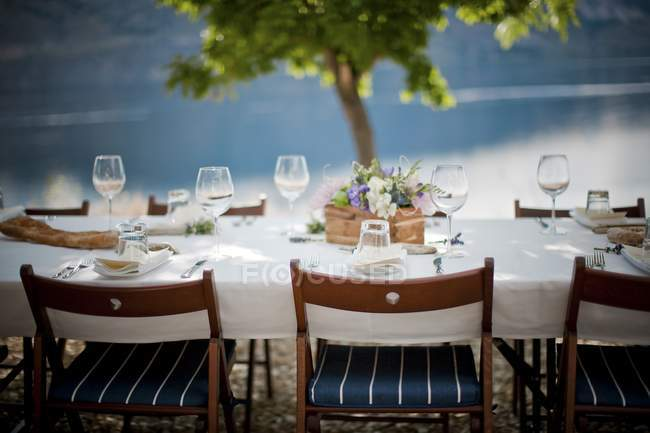 Festive served dining table beside lake — Stock Photo