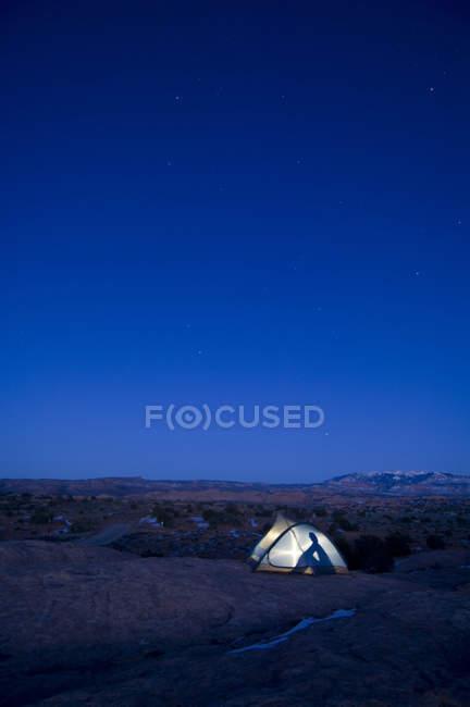 Beleuchteten Zelt mit menschliche Silhouette unter Sternenhimmel — Stockfoto