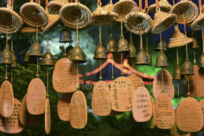 Lucky charms in form of small bells, wicker hats and wooden plates with Chinese hand writing at Shenyuan in Shaoxing — Stock Photo