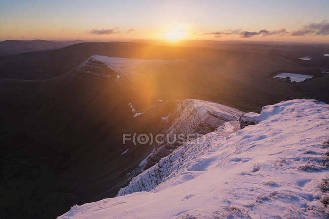 Snowcapped mountain landscape with setting sun in cloudy sky — Stock Photo