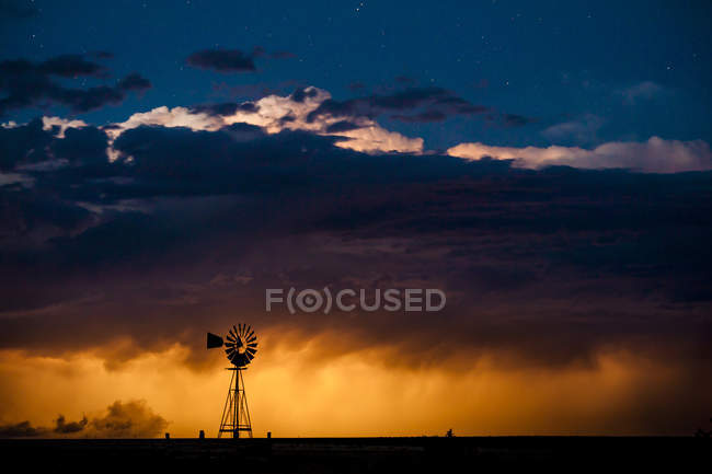Windmill silhouette on hill with vivid sunset sky — Stock Photo