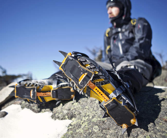Mountaineer with crampons on rest on rocky outcrop in White Mountains of New Hampshire — Stock Photo