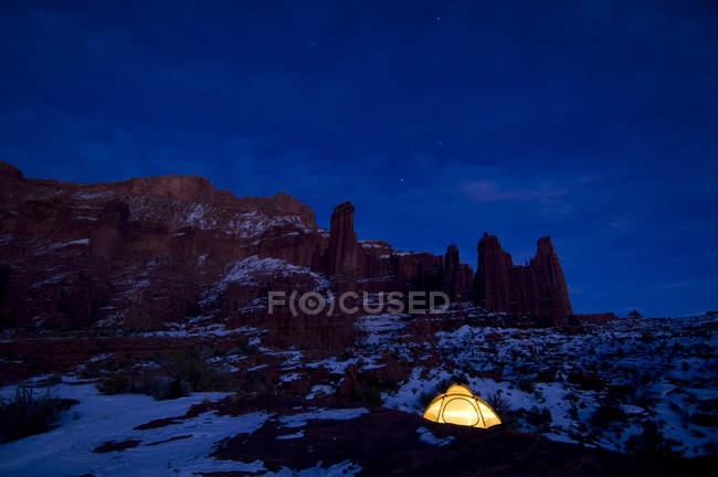 Glowing tent below rock formations illuminated at night — Stock Photo