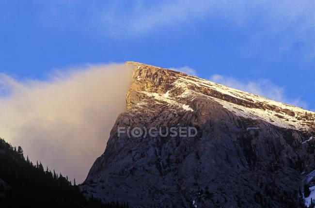 Nuages entourant le sommet de la montagne dans les Rocheuses canadiennes — Photo de stock
