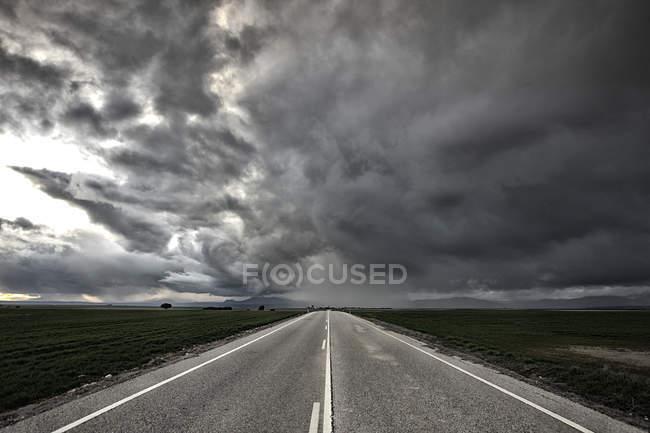 Diminshing vue en perspective du chemin de l'aphalt marquée sous le ciel nuageux — Photo de stock