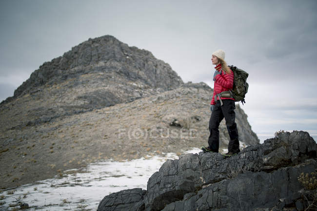 Young woman hiking with backpack in snowy mountains — Stock Photo