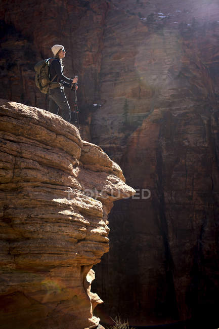 Young woman in hat and sunglasses hiking red rock of Zion National Park — Stock Photo