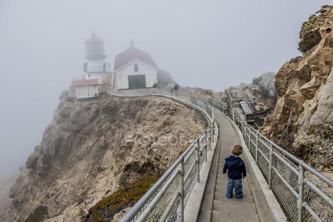 Boy walking down steps on foggy day toward Point Reys lighthouse in Point Reys National Park, Califorinia — Stock Photo