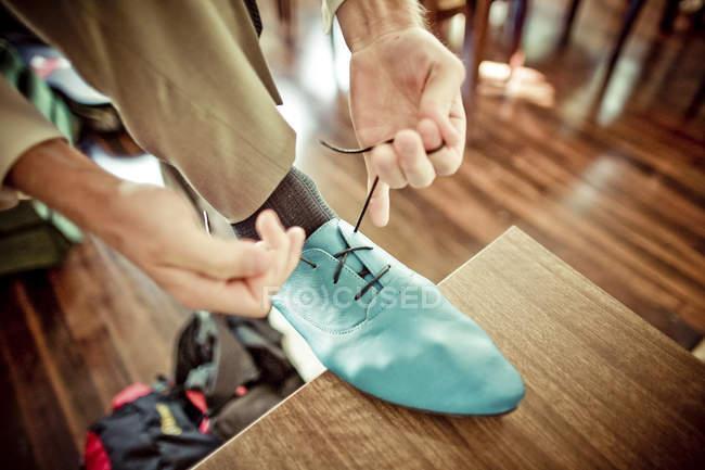 Homme attachant lacets sur chaussure bleu — Photo de stock