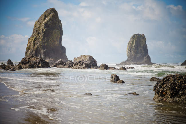 Rock formations on beach under blue cloudy sky — Stock Photo