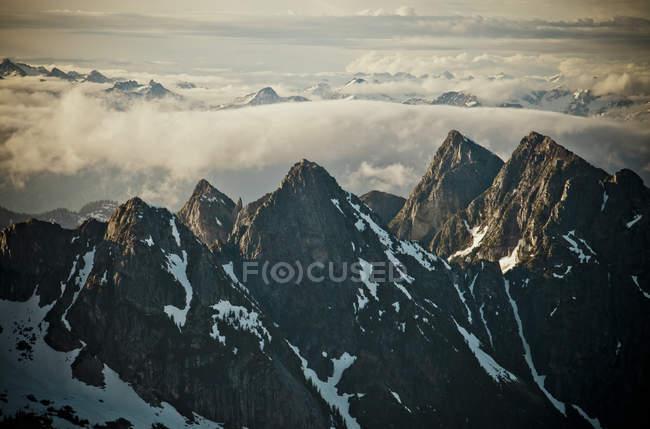 Montagne innevate con nuvole al sole — Foto stock