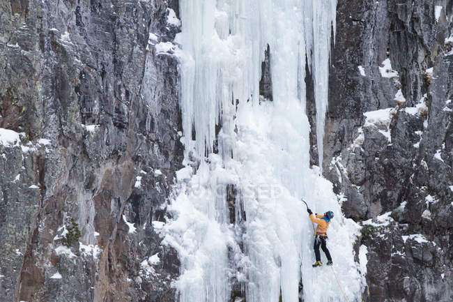 Ice climber ascending frozen waterfall — Stock Photo