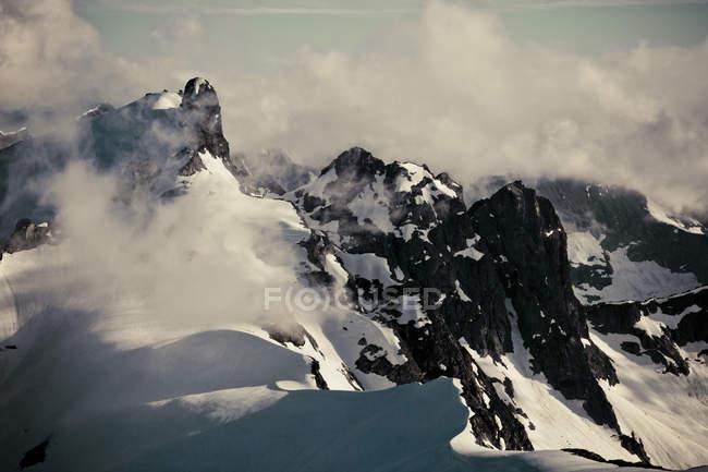 Cime innevate, circondati con le nubi — Foto stock