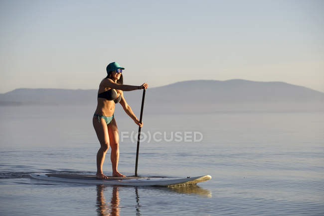 Жінка paddleboarding на озеро Тахо раннього ранку на спокійних водах склоподібного, Ca — стокове фото