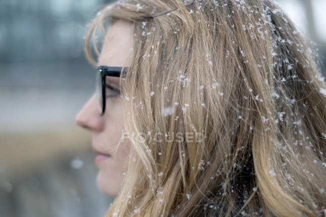 Young woman with glasses collecting snowflakes in profile head shot — Stock Photo