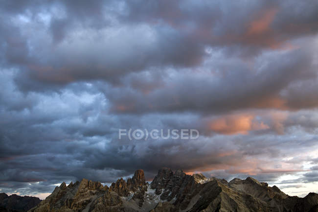 Cloudy sunset sky above rocky mountains — Stock Photo