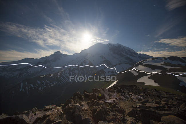 Hikers headlamp trail crosses Burroughs Mountain in backlit — Stock Photo
