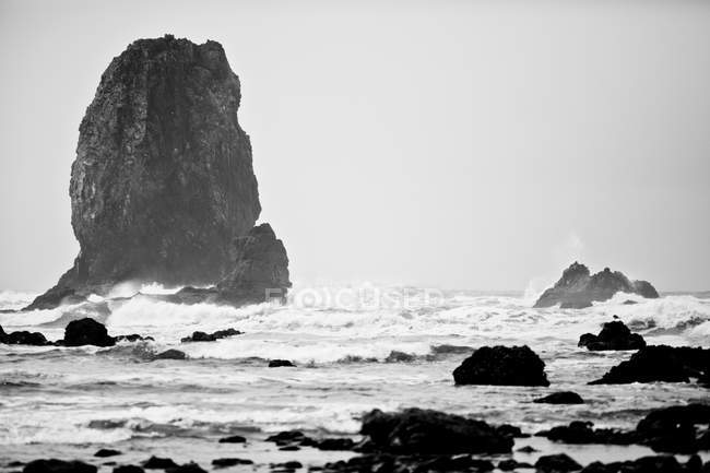 Monolith rock on beach with surf waves — Stock Photo