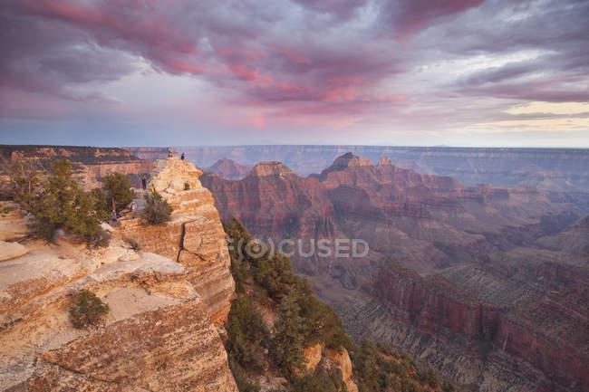 Туристи, дивлячись на панорамою заходу сонця і зйомку Гранд-Каньйон, Арізона — стокове фото