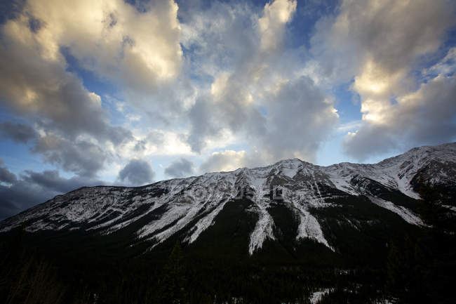 Cloudy sky over snowcapped mountain tops — Stock Photo