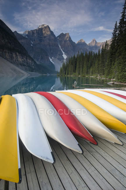Rental canoes piled up on dock near Moraine Lake with mountains on background — Stock Photo