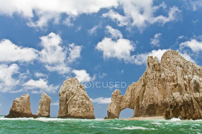 Bildung Felsbogen im azurblauen Wasser mit blauen Wolkenhimmel — Stockfoto