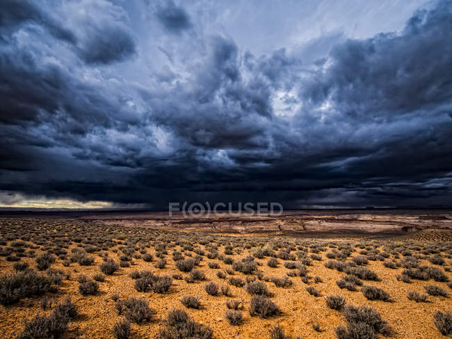 Dark dramatic sky with storm clouds over a desert landscape — Stock Photo