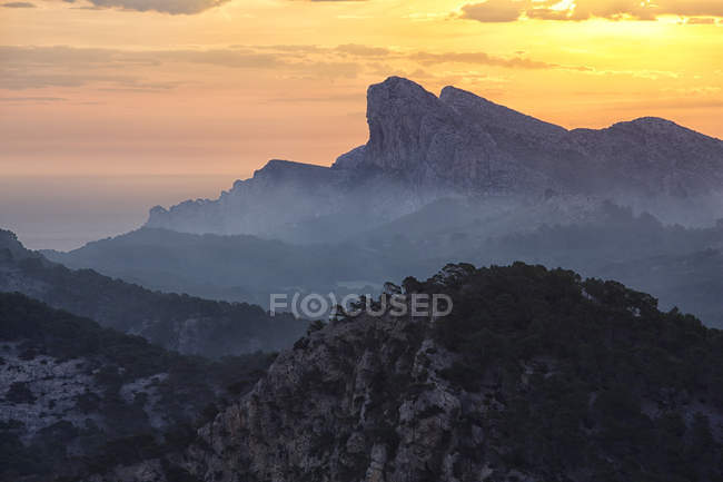 Mountain landscape with sun lighted evening sky — Stock Photo
