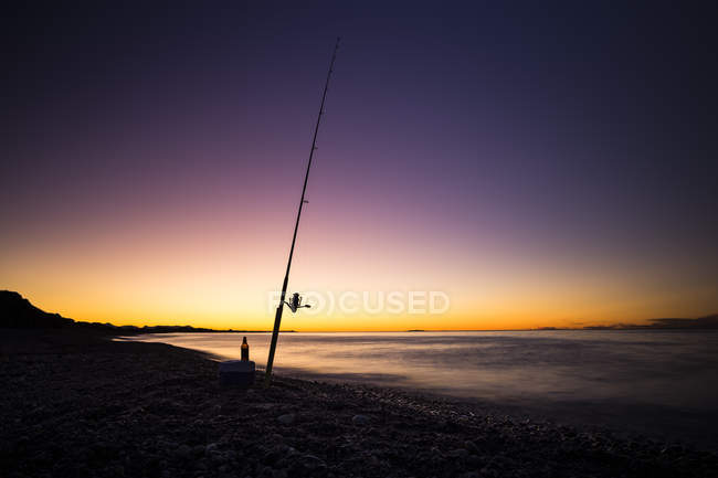 Glowing evening sky with fishing rod silhouette on shore — Stock Photo