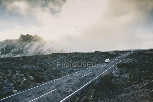 Автомобиль едет на туманный дороге, в окружении вулканических пород — стоковое фото