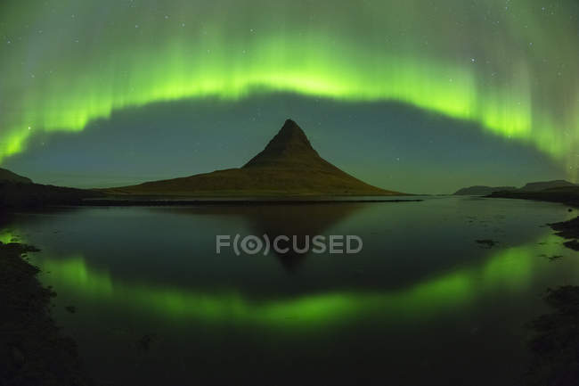 Cortina de luces del norte sobre montaña de Kirkjufell en Islandia occidental - foto de stock